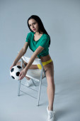 Photo sensual girl holding football ball while sitting on chair on grey