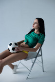 Photo beautiful sexy girl holding football ball while sitting on chair on grey