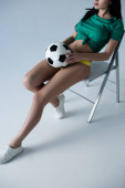 Photo cropped view of sexy woman holding football ball while sitting on chair on grey