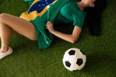 cropped view of sexy woman lying with football ball and brazilian flag on green grass