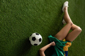 cropped view of sexy girl lying with brazilian flag and football ball on green grass