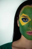 Fotografie atraktivní fanynka fotbalu s malovanou brazilskou vlajkou na obličeji na šedé