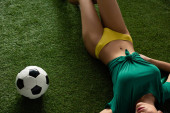 Photo cropped view of sexy girl lying with football ball on green grass
