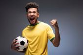 izgatott férfi afro-amerikai futball rajongó sárga pólóban tartja labda szürke