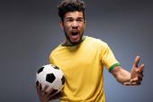 rozzlobený africký americký fotbalový fanoušek ve žlutém tričku křičící a držící míč na šedé
