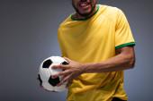 vágott kilátás érzelmi labdarúgó ventilátor sárga pólóban gazdaság labda szürke