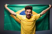 aufgeregter afrikanisch-amerikanischer Fußballfan schreit und hält brasilianische Flagge auf grau