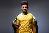 veselý africký americký fotbalový fanoušek drží brazilskou vlajku na šedé