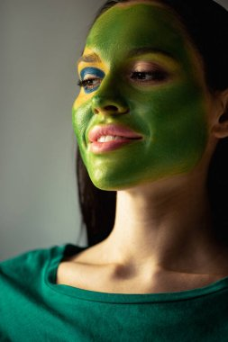 Attractive smiling woman with painted brazilian flag on face  isolated on grey stock vector