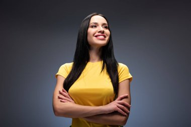proud smiling girl standing with crossed arms on grey