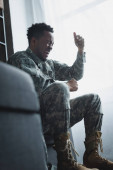stressed african american soldier screaming and holding army badge at home, suffering from PTSD