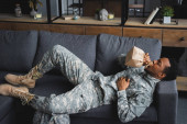 african american soldier in military uniform holding paper bag while having panic attack  at home