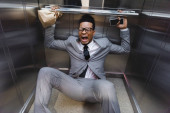 Fényképek rémült sikoltozó afro-amerikai üzletember okostelefonnal és papírzacskóval szenved pánikroham a liftben