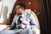 nervous african american businessman holding safety belt and having panic attack during flight on private plane
