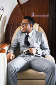 stressed african american businessman holding safety belt and having panic attack during flight on private plane