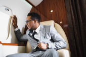 Worried african american businessman holding safety belt and having panic attack during flight on private plane
