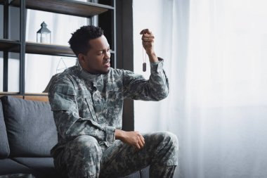Stressed african american soldier looking at army badge at home, suffering from PTSD stock vector