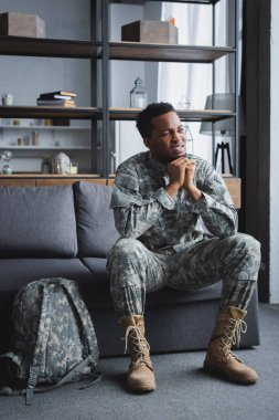 Sad african american soldier in military uniform suffering from PTSD at home stock vector