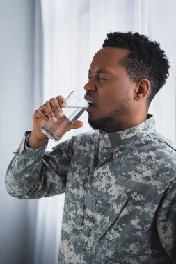 Stressed african american soldier drinking water and suffering from PTSD at home stock vector