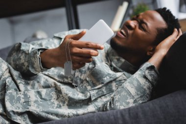 Stressed african american soldier crying while holding army badge and smartphone, suffering from PTSD at home stock vector