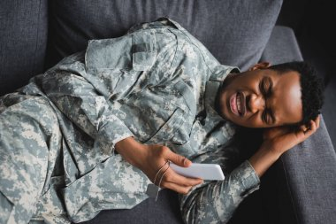 Lonely african american soldier crying while holding army badge and smartphone, suffering from PTSD at home stock vector