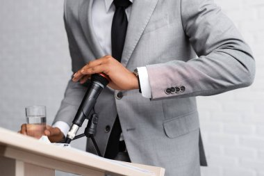 cropped view of nervous african american speaker holding glass of water and covering microphone during business conference