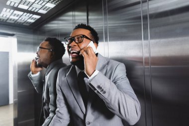 crying african american businessman talking on smartphone and suffering from panic attack in elevator