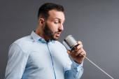 bearded man taking while holding tin can isolated on grey