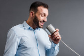 happy bearded man talking while holding tin can isolated on grey