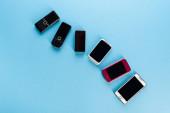 Draufsicht auf alte Mobiltelefone und moderne Smartphones auf blau, Evolutionskonzept