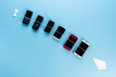 top view of retro mobile phones and modern smartphones on blue, evolution concept