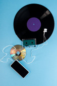 Photo top view of vinyl record, compact disk, earphones, audio tape and smartphone with blank screen on blue, evolution concept