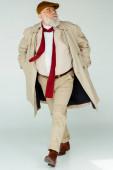 Plná délka pohledný senior muž v trenč kabát chůze na bílém pozadí