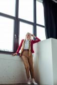 Plná délka elegantní starší ženy stojící u okna ve fotostudiu