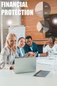 selektivní zaměření usměvavých multikulturních podnikatelů sedících v konferenčním sále a sledujících notebook, finanční ochrana ilustrace