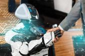 oříznutý pohled na obchodníka, jak si potřásá rukama s usměvavým robotem v kanceláři