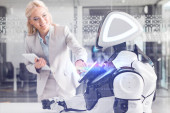 Photo smiling businesswoman operating robot while holding digital tablet, cyber illustration