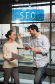 Photo cheerful asian businesswoman holding papers and talking to handsome colleague with digital tablet, seo illustration