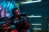 nízký úhel pohledu na smíšeného závodního cyberpunk hráče na motorce