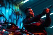 nízký úhel pohledu smíšeného závodu cyberpunk hráč na motocyklu mířící pistole