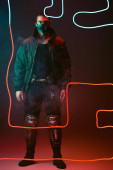 mixed race cyberpunk player in protective mask standing near red neon lighting on black