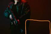 Fotografie abgeschnittene Ansicht eines Cyberpunk-Spielers mit Pistole in der Nähe von Neonbeleuchtung auf Schwarz