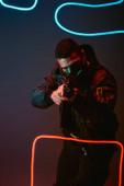 mixed race cyberpunk player in protective mask aiming gun near neon lighting on black