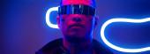 panoramic shot of mixed race cyberpunk player in futuristic glasses near blue neon lighting