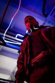 low angle view of bi-racial cyberpunk player standing near blue neon lighting
