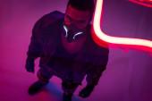 overhead view of bi-racial cyberpunk player in mask near red neon lighting