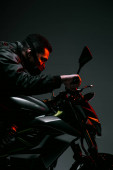 Fotografie boční pohled na smíšený závod cyberpunk hráč v masce na koni motocykl na šedé