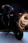 Fotografie selektivní zaměření nebezpečné smíšené rasy cyberpunk hráč v masce na koni motocykl v blízkosti jiskry na černé a bílé