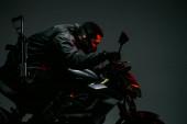 Fotografie profil ozbrojeného bi-rasového cyberpunkového hráče v masce na koni motocyklu na šedi