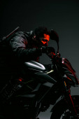 side view of armed bi-racial cyberpunk player in mask riding motorcycle on grey